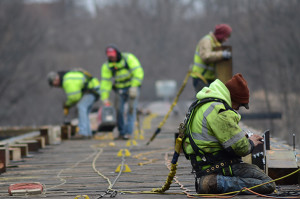 Construction workers tethered to bridge deck