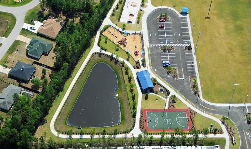 Aerial view of parking lot next to park and small pond