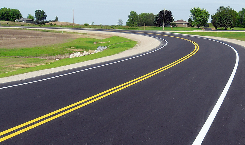Freshly paved and painted curving rural road