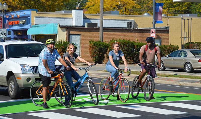 Individuals on bikes using a bike box.