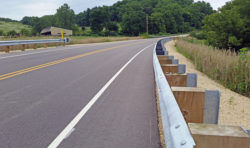 Shoulder of paved roadway with focus on guardrail