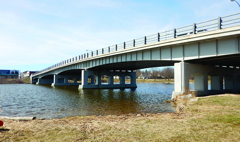 Bridge spanning river perspective from shore near water