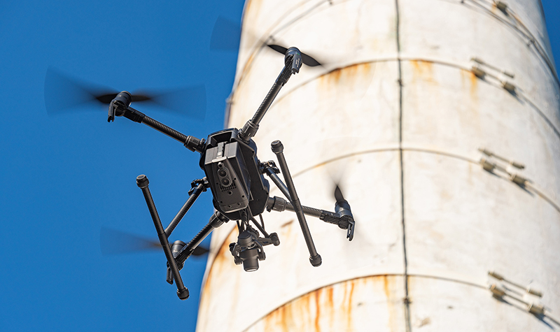 Drone hovering near smokestack