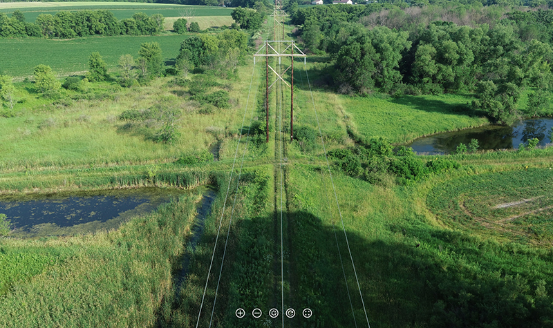 A high-resolution aerial 360° image reveals an elevated access road with steep sides surrounded by marshy ground